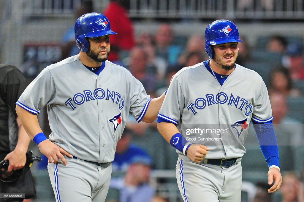 Darrell Seciliani #9 of the Toronto Blue Jays grimaces as he is congratulated by Kendrys Morales #8 after hitting a third inning two-run home run against the Atlanta Braves at SunTrust Park on May 18, 2017 in Atlanta, Georgia.