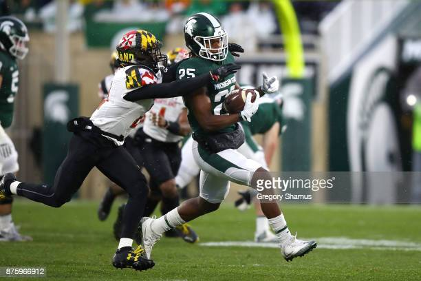 Darrell Stewart Jr #25 of the Michigan State Spartans looks for yards after a first half catch in front of Antoine Brooks Jr #25 of the Maryland...