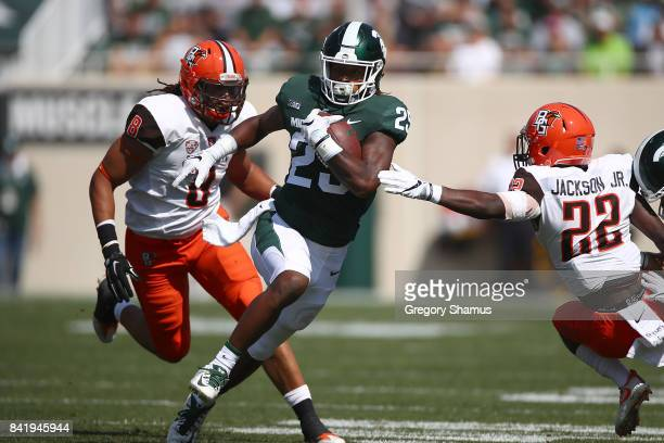 Darrell Stewart Jr #25 of the Michigan State Spartans tries to avoid a tackle by Robert Jackson Jr #22 of the Bowling Green Falcons at Spartan...