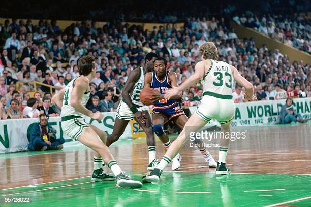 Darrell Walker of the New York Knicks drives to the basket against Danny Ainge and Larry Bird of the Boston Celtics during a game played in 1984 at...