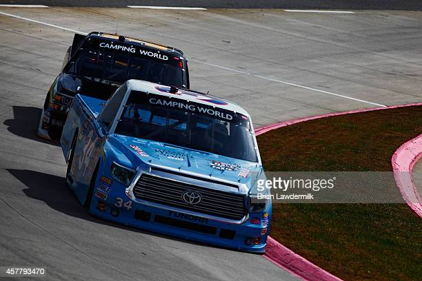 Darrell Wallace, Jr., driver of the 2015 NASCAR Hall of Fame Inductee Wendell Scott Toyota, leads Ben Kennedy, driver of the Heater.com Chevrolet,...