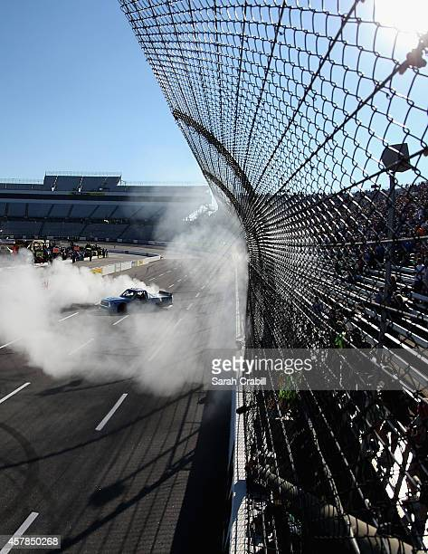 Darrell Wallace, Jr., driver of the 2015 NASCAR Hall of Fame Inductee Wendell Scott Toyota, celebrates with a burnout after winning the NASCAR...