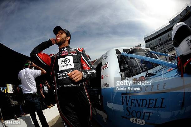 Darrell Wallace, Jr., driver of the 2015 NASCAR Hall of Fame Inductee Wendell Scott Toyota stands in the garage area during practice for the NASCAR...
