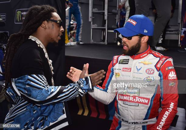 Darrell Wallace Jr driver of the Farmer John Chevrolet meets Migos prior to the Monster Energy NASCAR Cup Series Auto Club 400 at Auto Club Speedway...
