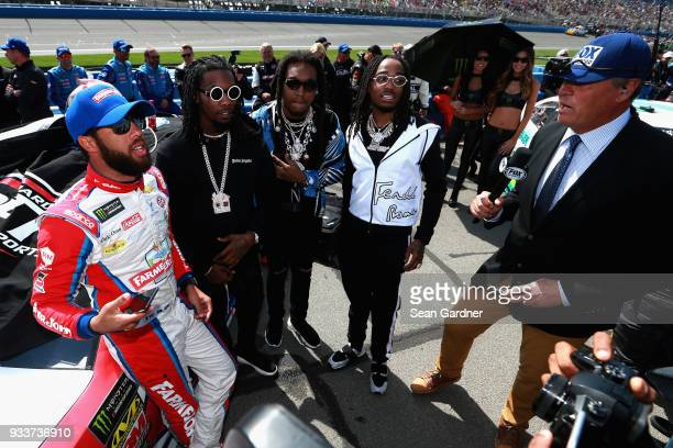 Darrell Wallace Jr driver of the Farmer John Chevrolet meets with the Migos on pit road during the Monster Energy NASCAR Cup Series Auto Club 400 at...