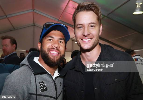 Darrell Wallace Jr driver of the Farmer John Chevrolet poses for a photo with Justin Hartley during the driver's meeting prior to the Monster Energy...