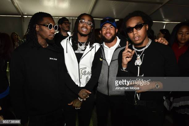 Darrell Wallace Jr driver of the Farmer John Chevrolet poses with Migos during the Monster Energy NASCAR Cup Series Auto Club 400 at Auto Club...