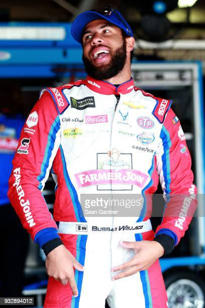 Darrell Wallace Jr driver of the Farmer John Chevrolet stands in the garage during practice for the Monster Energy NASCAR Cup Series Auto Club 400 at...