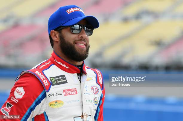 Darrell Wallace Jr driver of the Farmer John Chevrolet walks on a the grid during qualifying for the Monster Energy NASCAR Cup Series Auto Club 400...