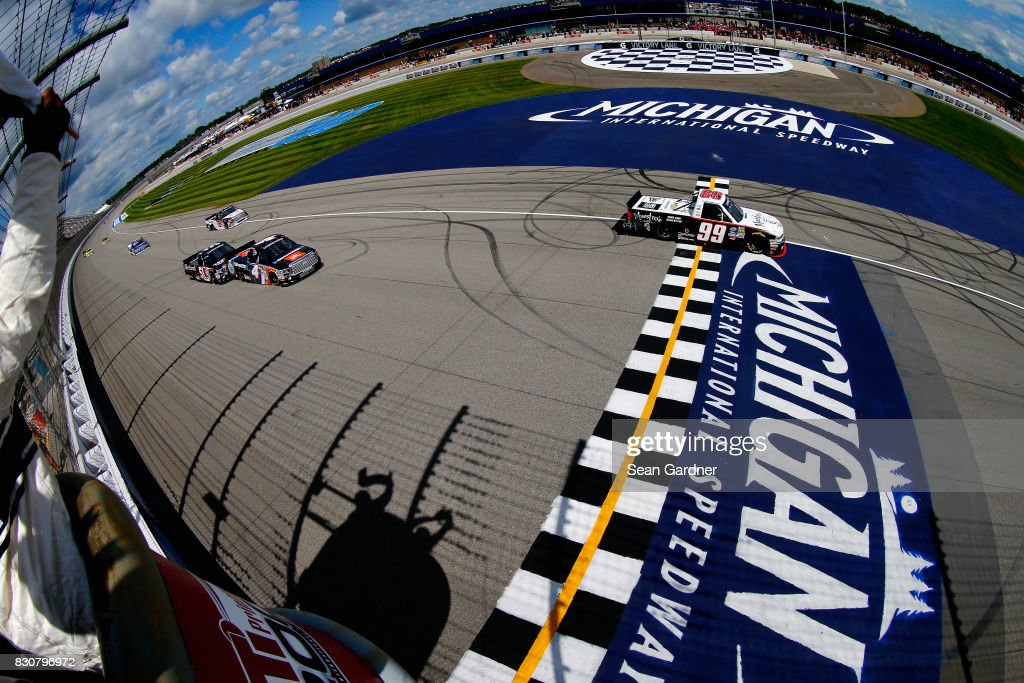 Darrell Wallace Jr., driver of the #99 Maestro's Classic Chevrolet, takes the checkered flag to win the NASCAR Camping World Truck Series LTi Printing 200 at Michigan International Speedway on August 12, 2017 in Brooklyn, Michigan.