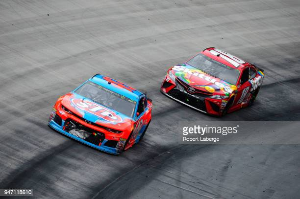 Darrell Wallace Jr driver of the STP Chevrolet races Kyle Busch driver of the Skittles Toyota during the rain delayed Monster Energy NASCAR Cup...