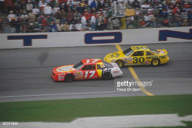 Darrell Waltrip drives his Tide car against the Michael Waltrip Country Time car during the Daytona 500 at the Daytona Speedway on February 19 1989...