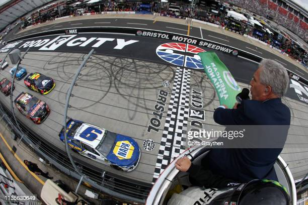Darrell Waltrip waves the green flag as Chase Elliott driver of the NAPA Auto Parts Chevrolet leads the field at the start of the Monster Energy...