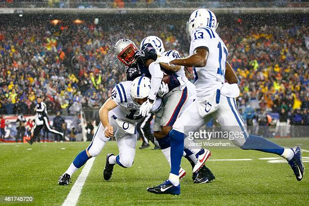 Darrelle Revis of the New England Patriots is tackled by Andrew Luck of the Indianapolis Colts after intercepting Luck's pass in the third quarter of...