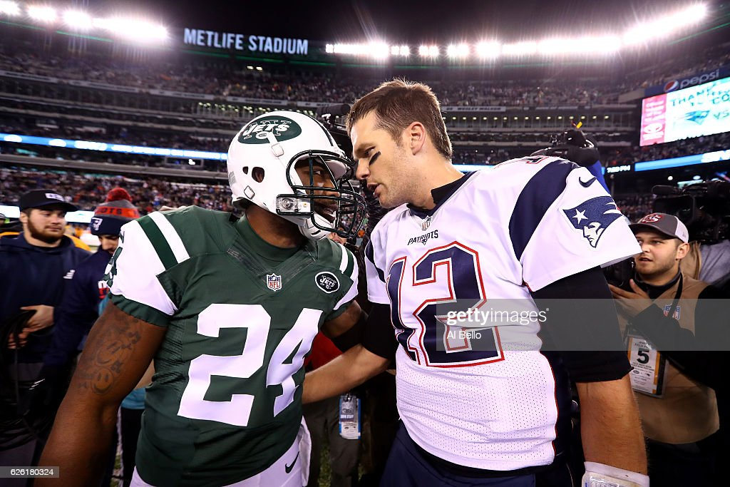 Darrelle Revis #24 of the New York Jets talks with Tom Brady #12 of the New England Patriots after their game at MetLife Stadium on November 27, 2016 in East Rutherford, New Jersey. The New England Patriots defeated the New York Jets with a score of 22 to 17.