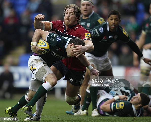Darren Allinson of London Irish feels the force of a challenge from Andy Powell of Sale Sharks during the Aviva Premiership match between London...