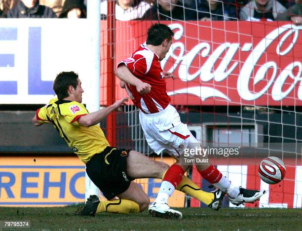 Darren Ambrose of Charlton Athletic opens the scoring while Tommy Smith of Watford challenges action during the Coca-Cola Championship match between...