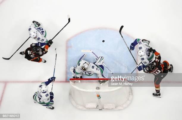Darren Archibald Henrik Sedin Jacob Markstrom and Alex Biega of the Vancouver Canucks defend against Adam Henrique and Ondrej Kase of the Anaheim...