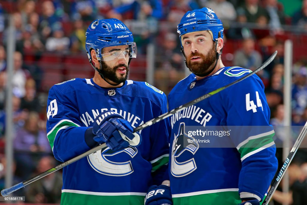 Darren Archibald #49 of the Vancouver Canucks talks with teammate Erik Gudbranson #44 during their NHL game against the Colorado Avalanche at Rogers Arena February 20, 2018 in Vancouver, British Columbia, Canada. Colorado won 5-4.