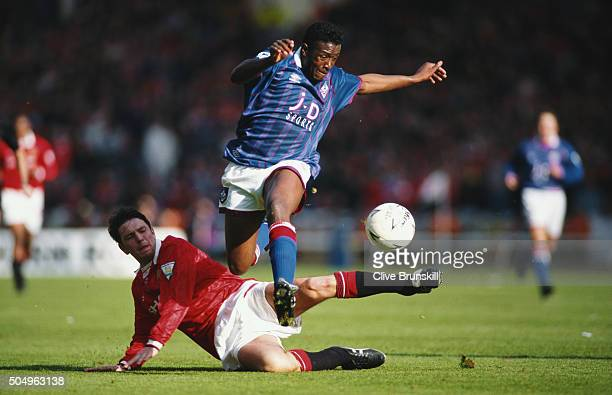 Darren Beckford of Oldham Athletic hurdles the challenge of Lee Sharpe of Manchester United during the 1994 FA Cup Semi Final at Wembley Stadium on...