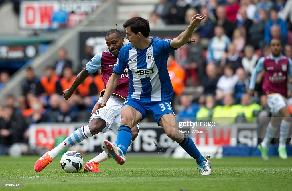 Darren Bent of Aston Villa (L) scores the opening goal past Paul Scharner of Wigan Athletic during the Barclays Premier League match between Wigan Athletic and Aston Villa at DW Stadium on May 19, 2013 in Wigan, England.