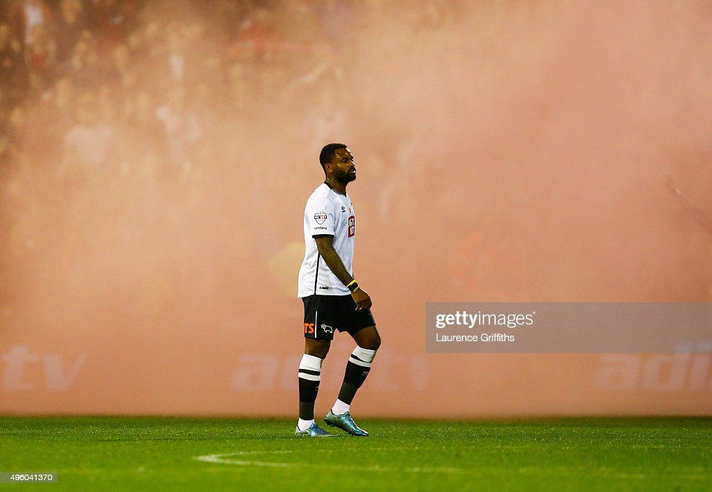 Darren Bent of Derby County looks dejected as he walks through smoke from flares after the Sky Bet Championship match between Nottingham Forest and Derby County at City Ground on November 6, 2015 in Nottingham, England.