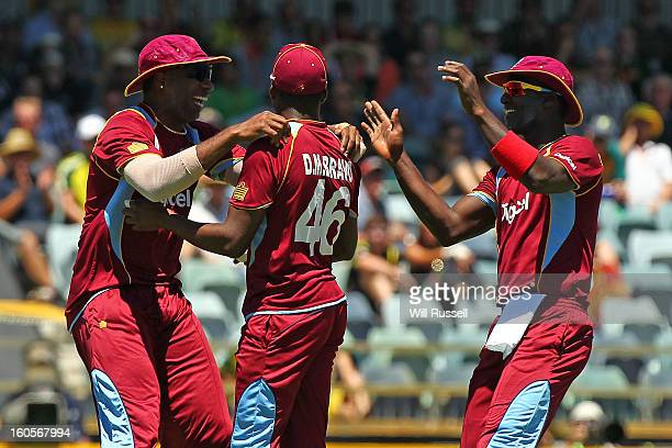 Darren Bravo of the West Indies is congratulated after taking a catch off Usman Khawaja during game two of the Commonwealth Bank One Day...