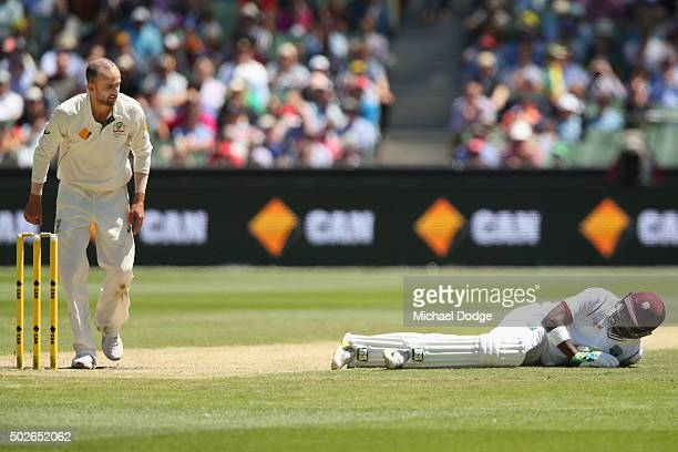 Darren Bravo of the West Indies lays on the pitch next to Nathan Lyon of Australia after ducking a ball hit by Carlos Brathwaite of the West Indies...