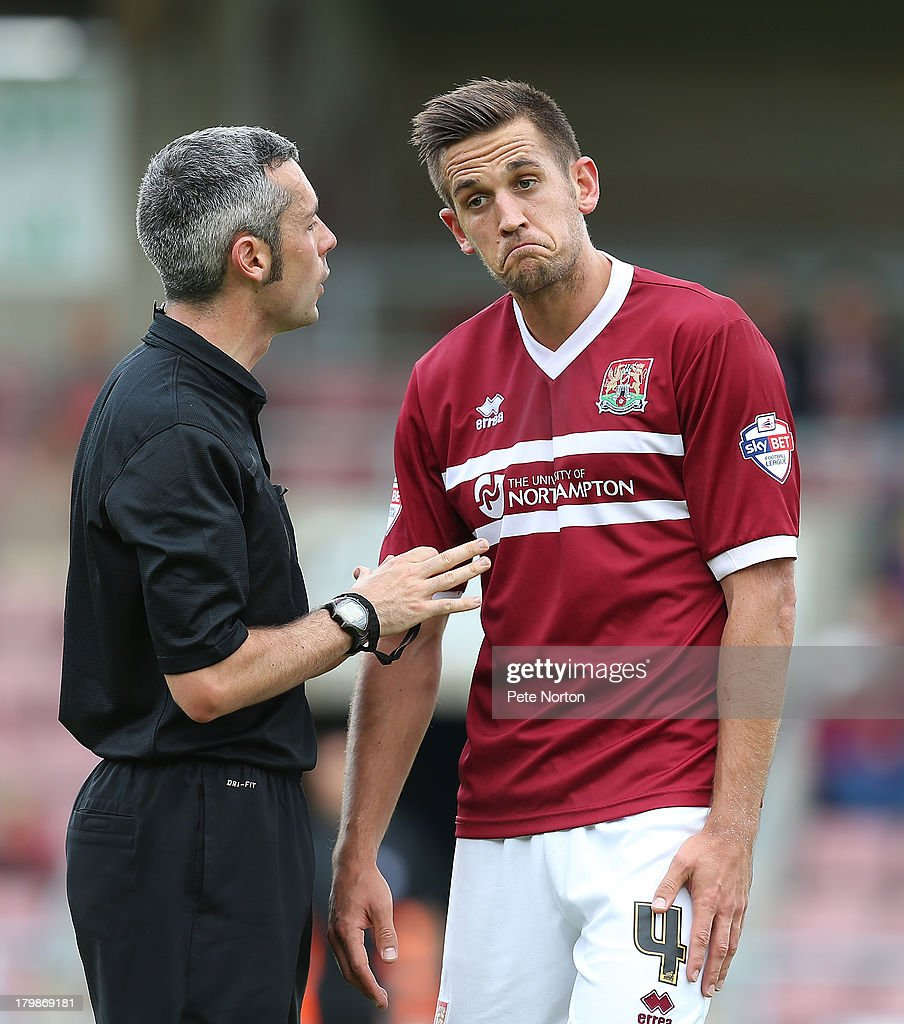 Darren Carter of Northampton Town is spoken to by Referee Sebastian Stockbridge during the Sky Bet League Two match between Northampton Town and Scunthorpe United at Sixfields Stadium on September 7, 2013 in Northampton, England.