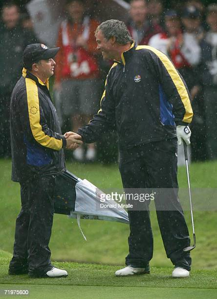 Darren Clarke of Europe is congratulated on his victory on the 16th green by European Team Captain Ian Woosnam during the morning fourballs on the...