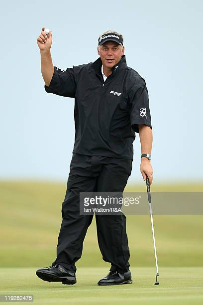 Darren Clarke of Northern Ireland acknowledges the crowd after putting out on the 12th hole during the third round of The 140th Open Championship at...