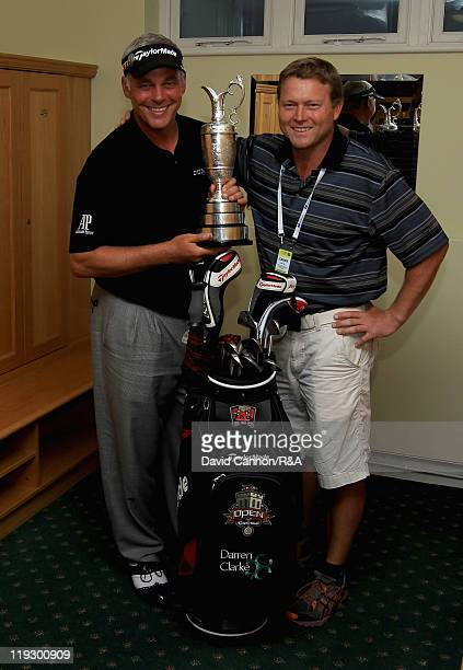 Darren Clarke of Northern Ireland and his caddie John Mulrooney pose with the Claret Jug in the locker room following his victory at the end of the...