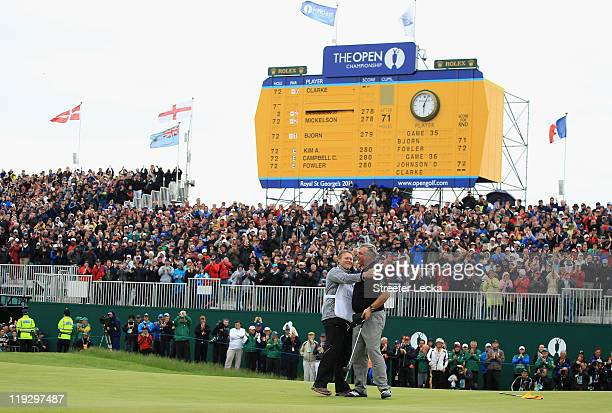 Darren Clarke of Northern Ireland embraces his caddy John Mulrooney on the 18th green following his victory during the final round of The 140th Open...
