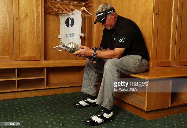 Darren Clarke of Northern Ireland looks at the Claret Jug in the locker room following his victory at the end of the final round of The 140th Open...