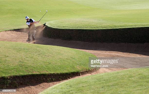 Darren Clarke of Northern Ireland plays out from a bunker of the third hole during the practice round prior to the 2014 Alfred Dunhill Links...