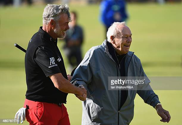 Darren Clarke of Northern Ireland shakes hands with Arnold Palmer during the Champion Golfers' Challenge ahead of the 144th Open Championship at The...