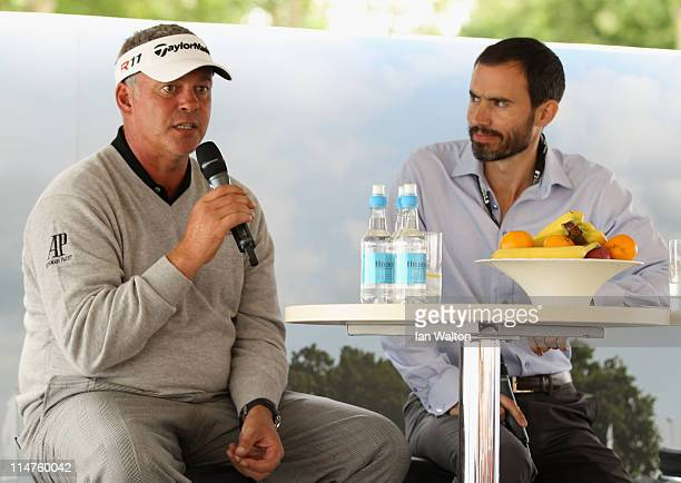 Darren Clarke of Northern Ireland talks with Andrew Cotter during a Q A session in the tented village during the first round of the BMW PGA...