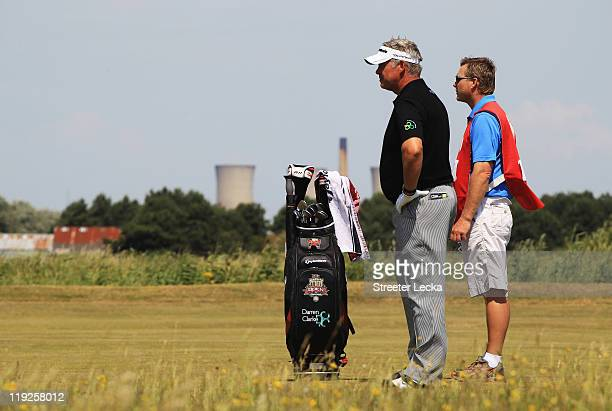 Darren Clarke of Northern Ireland waits with caddy John Mulrooney on the 14th hole during the second round of The 140th Open Championship at Royal St...