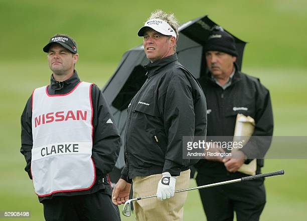 Darren Clarke of Northern Ireland watches his shot on the sixth hole hole as Ewen Murray and Billy Foster look on during the Nissan Irish Open ProAm...