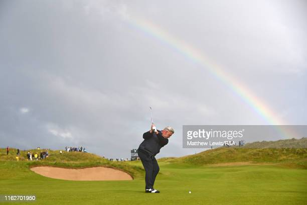 Darren Clarke of the Northern Ireland plays his second shot on the seventh hole under a rainbow during the first round of the 148th Open Championship...