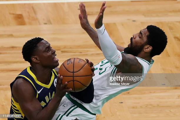 Darren Collison of the Indiana Pacers charges Kyrie Irving of the Boston Celtics during the first quarter at TD Garden on April 17 2019 in Boston...