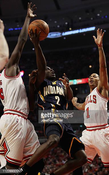 Darren Collison of the Indiana Pacers puts up a shot between Loul Deng and Derrick Rose of the Chicago Bulls in Game One of the Eastern Conference...