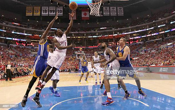 Darren Collison of the Los Angeles Clippers shoots over Draymond Green of the Golden State Warriors as Clipper DeAndre Jordan and Warrior David Lee...