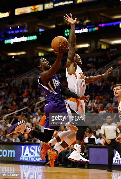 Darren Collison of the Sacramento Kings attempts a layup past Eric Bledsoe of the Phoenix Suns during the first half of the preseason NBA game at...
