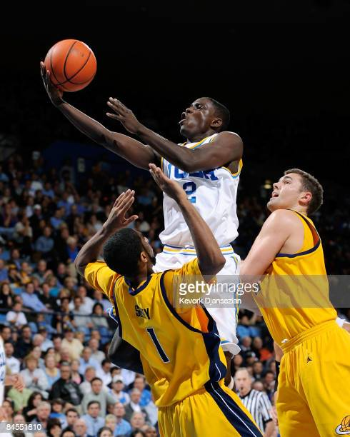 Darren Collison of the UCLA Bruins scores on a layup against D.J. Seeley and Harper Kamp of the University of California Golden Bears during the...