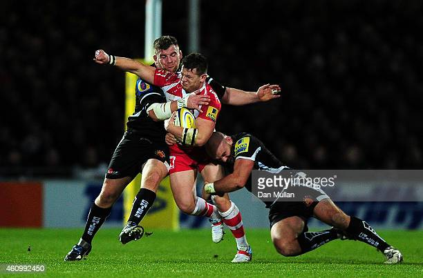 Darren Dawiduik of Gloucester is tackled by Moray Low and Jack Yeandle of Exeter Chiefs during the Aviva Premiership match between Exeter Chiefs and...