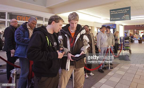 Darren Dodge left of New Brunswick Canada and Jerod Guyer of Windham wait at the front of a line outside the Apple Store at the Maine Mall in South...