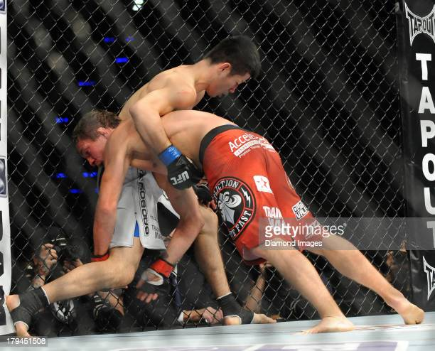 Darren Elkins and Hatsu Hioki wrestle on the cage during a featherweight bout during UFC Fight Night 27 Condit v Kampmann 2 at Bankers Life Field...