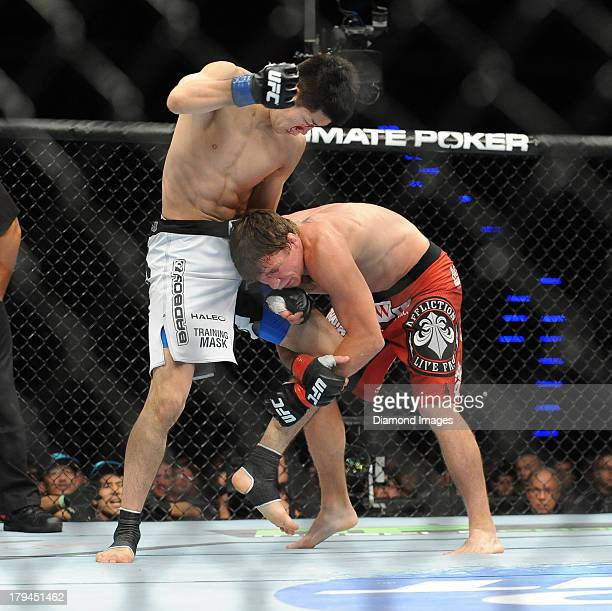 Darren Elkins goes for a single leg takedown of Hatsu Hioki during a featherweight bout during UFC Fight Night 27 Condit v Kampmann 2 at Bankers Life...