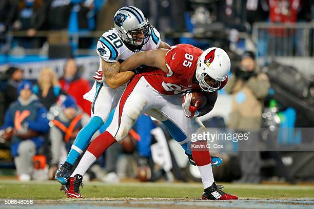 Darren Fells of the Arizona Cardinals runs with the ball for a touchdown as Kurt Coleman of the Carolina Panthers attempts to tackle him in the...